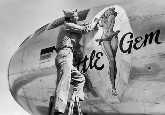 "Artist painting nose art on the B-29 Superfortress ""Little Gem"" during World War II"